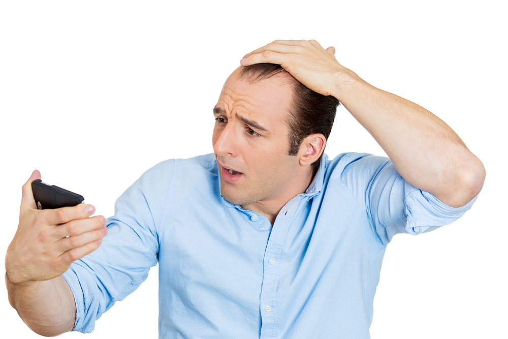 Closeup portrait of shocked man feeling head, surprised he is losing hair, receding hairline or seeing bad news on cellphone, isolated on white background. Negative facial expressions, emotion feeling